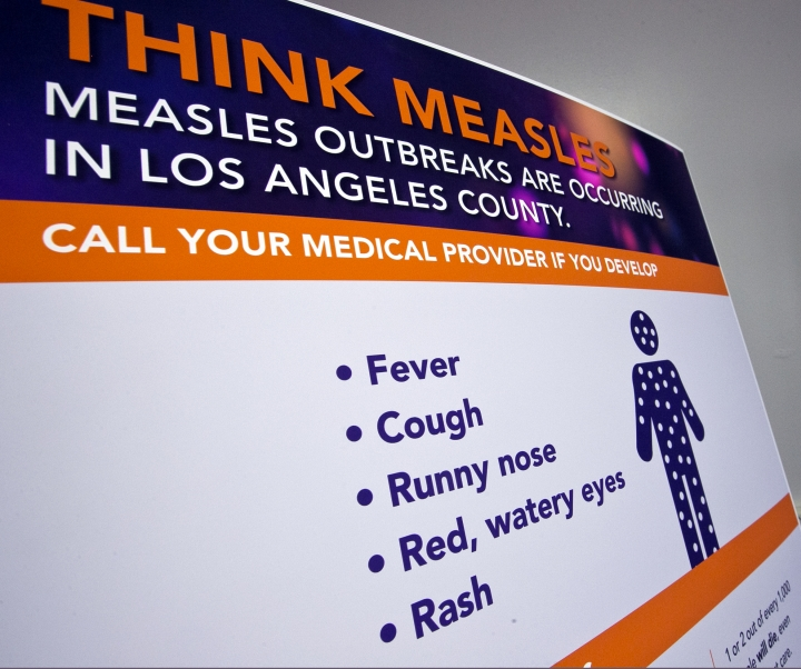 A poster released by Los Angeles County Department of Public Health is seen as experts answer questions regarding the measles response and the quarantine orders in Los Angeles Friday, April 26, 2019. Hundreds of students and staff members at two Los Angeles universities were sent home this week in one of the most sweeping efforts yet by public health authorities to contain the spread of measles in the United States, where cases have reached a 25-year high. (AP Photo/Damian Dovarganes)