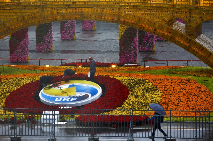 """Workers dismantle the Belt and Road Forum logo next to the """"Golden Bridge of Silk Road"""" structure outside the media center as leaders attendi the round table summit of the Belt and Road Forum chaired by Chinese President Xi Jinping in Beijing, Saturday, April 27, 2019. (AP Photo/Andy Wong)"""