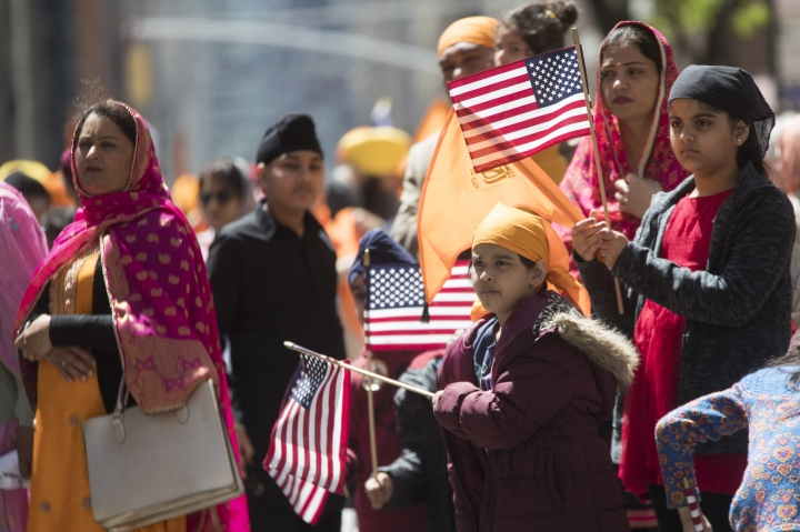 A Sikh American family watches participants march down Madison Avenue during the Sikh Day Parade, celebrating the Sikh holiday of Vaisakhi, Saturday, April 27, 2019, in New York. (AP Photo/Mary Altaffer)