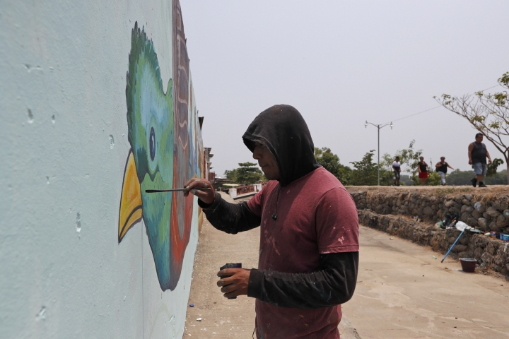 Mexican artist Julio Antonio Torres paints a mural on a wall near the Suchiate river on the border between Guatemala and Mexico in Ciudad Hidalgo, Chiapas state, Mexico, Saturday, April 27, 2019. The mural shows a Quetzal, a bird that takes migrants out of their homes and builds a future, according to its author. (AP Photo/Moises Castillo)