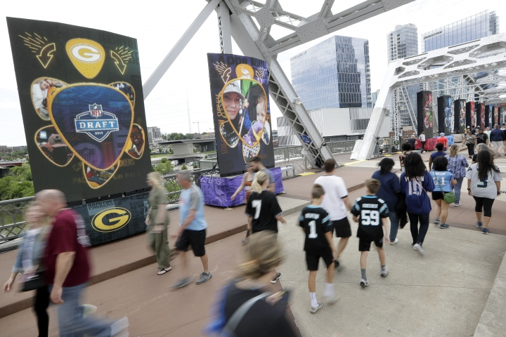 People walk on a bridge lined with video boards providing news on draft picks on the final day of the NFL football draft Saturday, April 27, 2019, in Nashville, Tenn. (AP Photo/Mark Humphrey)
