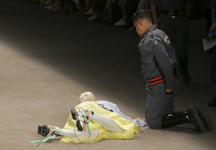 Model Tales Soares lies on the catwalk as a paramedic tends to him after he collapsed during Sao Paulo Fashion Week in Sao Paulo, Brazil, Saturday, April 27, 2019. A statement from organizers said that Soares died after taking ill while participating in the Sao Paulo's Fashion Week. (Leco Viana/Thenews2 via AP)
