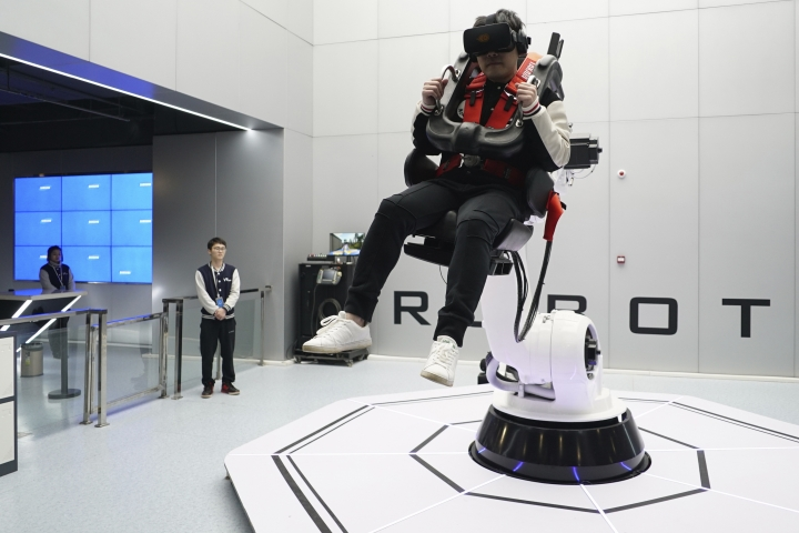 In this April 2, 2019, photo, a visitor rides a virtual roller coaster ride operated by a robotic arm in a VR theme park in Nanchang, China. One of the largest virtual reality theme parks in the world has opened its doors in southwestern China, sporting 42 rides and exhibits from VR bumper cars to VR shoot-em-ups. It's part of an effort by Beijing to get ordinary people excited about the technology - part of a long-term bet that VR will come into widespread use. (AP Photo/Dake Kang)