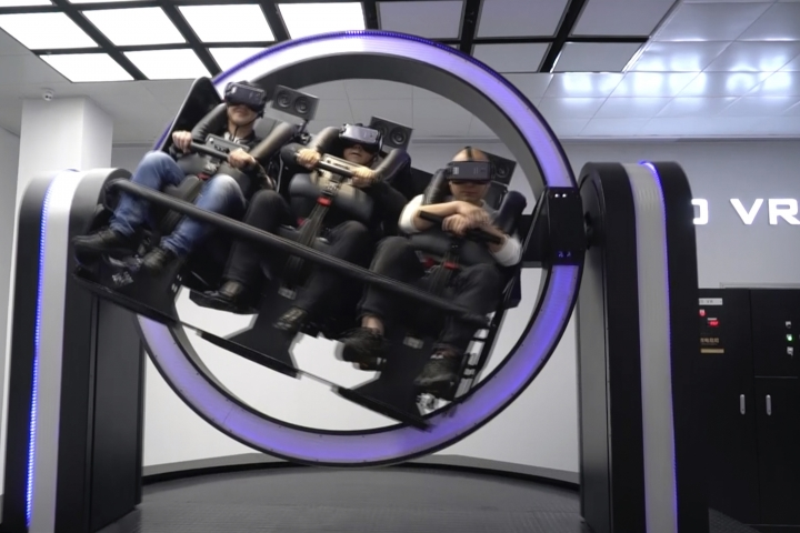 """In this April 2, 2019, photo, Liu Zixing, a mining ore businessman, right, rides a virtual reality """"gyroscope"""" in a VR theme park in Nanchang, China. One of the largest virtual reality theme parks in the world has opened its doors in southwestern China, sporting 42 rides and exhibits from VR bumper cars to VR shoot-em-ups. It's part of an effort by Beijing to get ordinary people excited about the technology - part of a long-term bet that VR will come into widespread use. (AP Photo/Dake Kang)"""