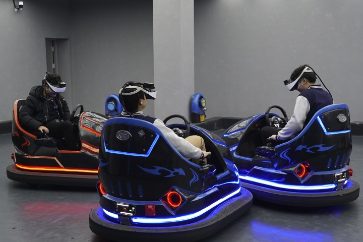 In this April 2, 2019, photo, visitors drive virtual reality bumper cars in a VR theme park in Nanchang, China. One of the largest virtual reality theme parks in the world has opened its doors in southwestern China, sporting 42 rides and exhibits from VR roller coasters to VR shoot-em-ups. It's part of an effort by Beijing to get ordinary people excited about the technology - part of a long-term bet that VR will come into widespread use. (AP Photo/Dake Kang)