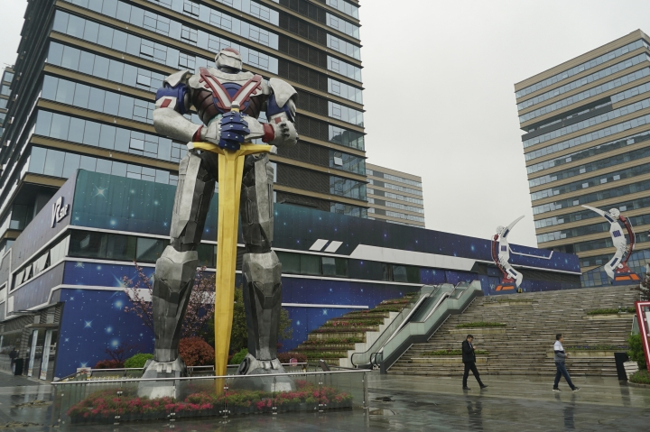 "In this April 2, 2019, photo, people walk by a giant robot statue at a virtual reality ""base"" in Nanchang, China. The city is trying to position itself as a leader in VR technology, opening one of the largest virtual reality theme parks in the world to get ordinary people excited about the technology. It's part of China's long-term bet that VR will come into widespread use. (AP Photo/Dake Kang)"