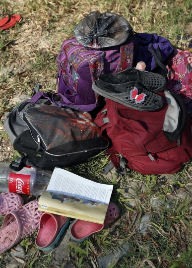 """A children's coloring book titled """"Lessons I learn from the Bible"""" lies amid the belongings of U.S.-bound Central American migrants on the bank of a river where members of the caravan wash clothes and bathe on a rest day near Mapastepec, Chiapas state, Mexico, Sunday, April 21, 2019. The outpouring of aid that once greeted Central American migrants as they trekked in caravans through southern Mexico has been drying up, so this group is hungrier, advancing slowly or not at all. (AP Photo/Moises Castillo)"""