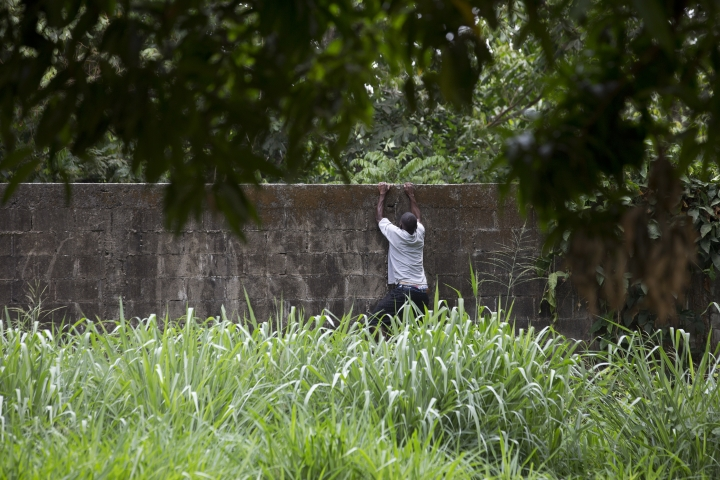 """A migrant climbs a wall to return to a migrant shelter in """"Feria Mesoamericana"""" park after buying food for his family in Tapachula, Chiapas state, Mexico, Friday, April 26, 2019. Migrants who still have money sometimes sneak out of the compound by jumping the wall and buying their own groceries to cook over open fires. (AP Photo/Moises Castillo)"""