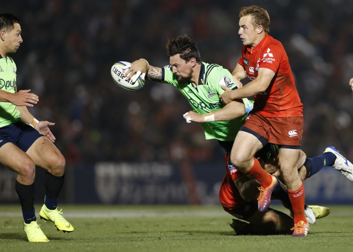 Highlanders' Elliot Dixon, center, passes the ball, tackled by Sunwolves' Hayden Parker during the Super Rugby game between the Highlanders and Sunwolves in Tokyo, Friday, April 26, 2019. (AP Photo/Shuji Kajiyama)