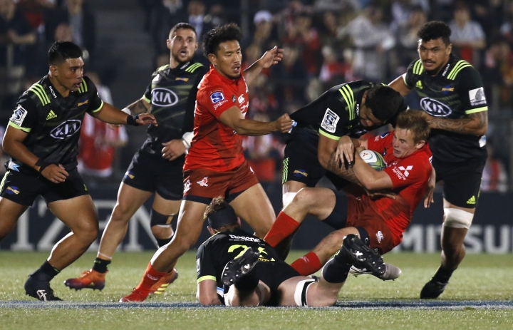 Sunwolves Hayden Parker, second from right, is tackled by Hurricanes defense during the Super Rugby game between the Hurricanes and Sunwolves in Tokyo, Friday, April 19, 2019. (AP Photo/Shuji Kajiyama)