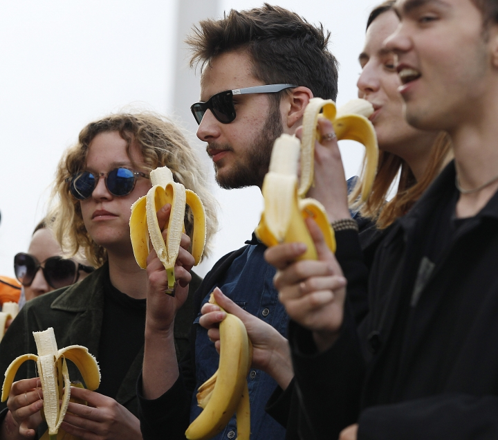 People with bananas demonstrate with others outside Warsaw's National Museum, Poland, Monday, April 29, 2019, to protest against what they call censorship, after authorities removed an artwork at the museum featuring the fruit, saying it was improper. (AP Photo/Czarek Sokolowski)