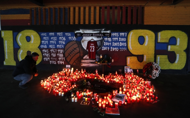 A man looks at candles placed near the Sparta stadium in Prague, Czech Republic, Monday, April 29, 2019, after the death of Czech soccer player Josef Sural. 28-year old Sural died and six other Alanyaspor players were injured after their van was involved in an auto accident at the town of Alanya, on Turkey's Mediterranean coast, on their way home from a game in Turkey's top-tier soccer league. (AP Photo/Petr David Josek)