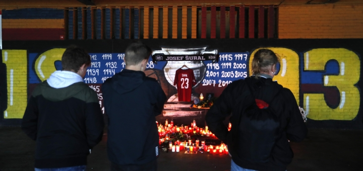 People look at candles placed near the Sparta stadium in Prague, Czech Republic, Monday, April 29, 2019, after the death of Czech soccer player Josef Sural. 28-year old Sural died and six other Alanyaspor players were injured after their van was involved in an auto accident at the town of Alanya, on Turkey's Mediterranean coast, on their way home from a game in Turkey's top-tier soccer league. (AP Photo/Petr David Josek)