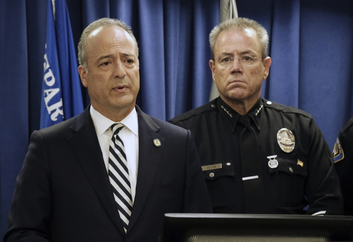 LAPD Chief Michel Moore, right looks on as United States Attorney Nick Hanna, talks during a news conference in Los Angeles on Monday, April 29, 2019. A terror plot by an Army veteran who converted to Islam and planned to bomb a white supremacist rally in Southern California as retribution for the New Zealand mosque attacks was thwarted, federal prosecutors said Monday. Mark Domingo, 26, an infantryman who served a combat stint in Afghanistan, was arrested by federal agents Friday while finalizing plans to plant a bomb at a Nazi rally that had been scheduled Sunday in Long Beach. (AP Photo/Richard Vogel)