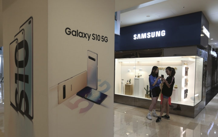 Middle school students watch their smartphones next to an advertisement of Samsung Electronics' Galaxy S10 5G smartphone at its shop in Seoul, South Korea, Tuesday, April 30, 2019. Samsung Electronics Co. says its operating profit for the last quarter declined more than 60% from a year earlier because of falling chip prices and sluggish demands for its display panels. (AP Photo/Ahn Young-joon)