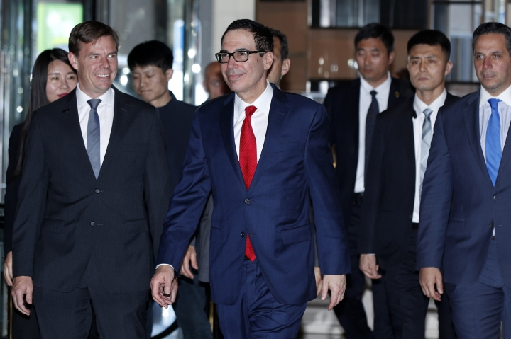 U.S. Treasury Secretary Steven Mnuchin, center, is escorted by bodyguards and officials as he arrives at a hotel in Beijing, Tuesday, April 30, 2019. Mnuchin arrived in China's capital to hold a new high-level trade talks with China on May 1. (AP Photo/Andy Wong)