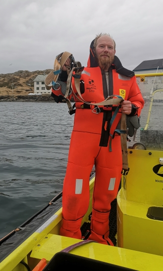 """CORRECTING NAME TO JOAR HESTEN - Norwegian fisherman Joar Hesten, who jumped into the frigid Arctic water to cut the harness from a beluga whale off the northern Norwegian coast Friday, April 26, 2019. The harness strap which features a mount for an action camera, says """"Equipment St. Petersburg"""" which has prompted speculation that the animal may have escaped from a Russian military facility. (Joergen Ree Wiig/Norwegian Direcorate of Fisheries Sea Surveillance Unit via AP)"""
