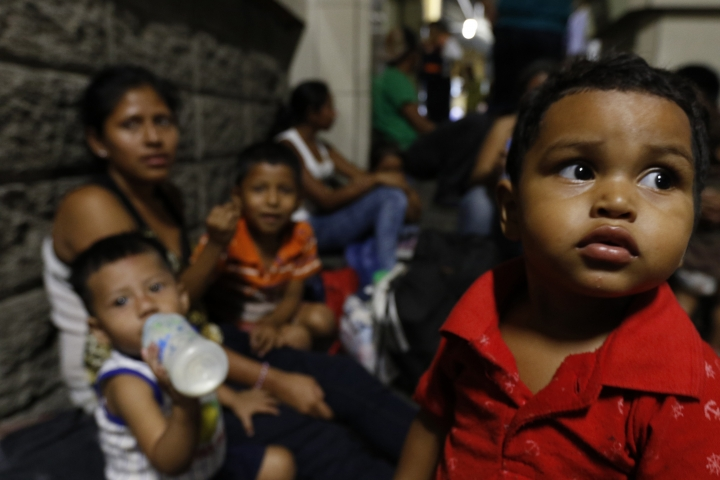 FILE - In this April 9, 2019 file photo, migrants planning to join a caravan of several hundred people setting out in hopes of reaching the distant United States, wait at the bus station in San Pedro Sula, Honduras. Calls for a new migrant caravan departing April 30 went largely unheeded as a relatively small group departed from Honduras one week after a raid by Mexican police resulted in hundreds of detentions and the dissolution of a previous caravan. (AP Photo/Delmer Martinez, File)