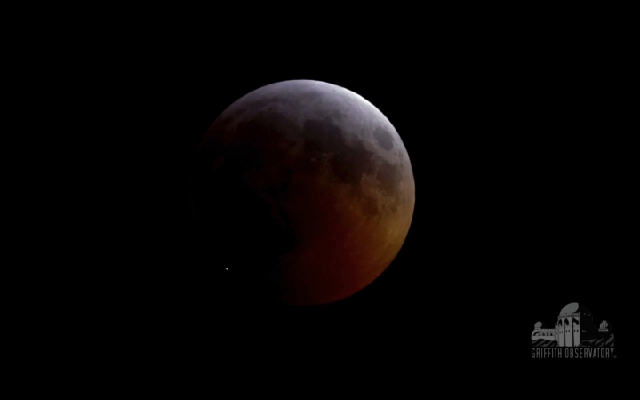 FILE - This image from video provided by Griffith Observatory in Los Angeles shows an impact flash on the moon, bottom left, during the lunar eclipse which started on Sunday evening, Jan. 20, 2019. On Tuesday, April 30, 2019, scientists reported the meteoroid hit the moon at 38,000 mph (61,000 kph), carving out a crater nearly 50 miles (15 meters) across. It was the first impact flash ever observed during a lunar eclipse. (Griffith Observatory via AP)