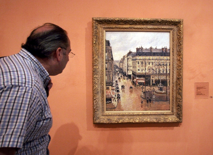 """FILE - This May 12, 2005 file photo shows an unidentified visitor viewing the Impressionist painting called """"Rue St.-Honore, Apres-Midi, Effet de Pluie"""" painted in 1897 by Camille Pissarro, on display in the Thyssen-Bornemisza Museum in Madrid. A federal judge in Los Angeles ruled Tuesday, April 30, 2019 that the museum that acquired the priceless, Nazi-looted painting in 1992 is the work's rightful owner, and not the survivors of the Jewish woman who surrendered it 80 years ago to escape the Holocaust. Under Spanish law, he ruled, the painting is legally the museum's, although he also criticized Spain, calling its decision to keep it """"inconsistent"""" with international agreements. The museum's U.S. attorney, Thaddeus Stauber, said he believes the decision finally puts an end to a bitter legal fight that has pitted the family of Lilly Cassirer against the museum for 20 years. (AP Photo/Mariana Eliano, File)"""