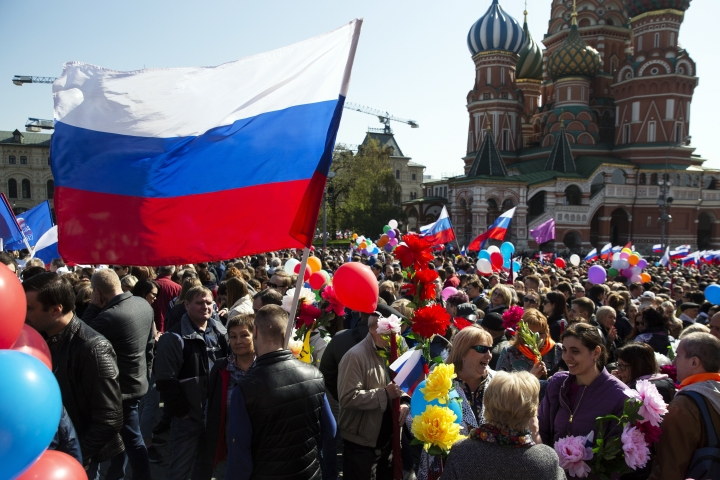 Balloons and flags fly over the crowd as people prepare to walk on Red Square in Moscow, Russia, Wednesday, May 1, 2019, with the St. Basil's Cathedral in the background. As in Soviet times, people paraded across Red Square on May Day, but instead of red flags with the Communist hammer and sickle, they waved the Russian tricolor. (AP Photo/Pavel Golovkin)