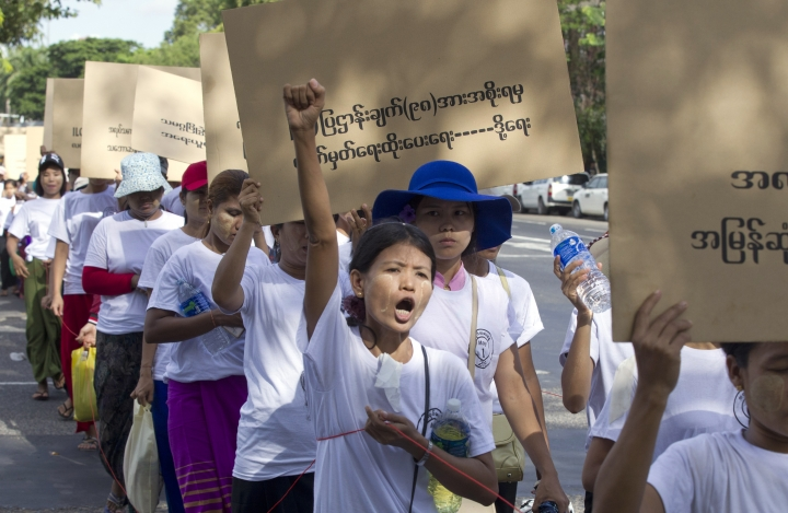 """Myanmar workers holding a placard read, """"Government to sign 98 facts of ILO law,"""" shout slogans during a marching ceremony Wednesday, May 1, 2019, in Yangon, Myanmar. Hundreds most of factory workers marched Wednesday to mark International Workers' Day asked for to get their labor rights. (AP Photo/Thein Zaw)"""