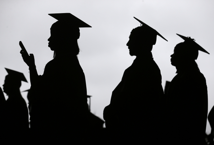 FILE - In this May 17, 2018, file photo, new graduates line up before the start of the Bergen Community College commencement at MetLife Stadium in East Rutherford, N.J. A college degree has long been a ticket to the U.S. middle class. Yet a new survey shows that college graduates aren't as likely as they once were to feel they belong to the middle class. (AP Photo/Seth Wenig, File)