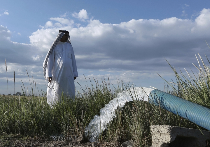In this Tuesday, April 23, 2019, photo, a farmer stands near a water pump on his farm in Youssifiyah, Iraq. In the farming region, just south of the capital, canals that were empty last year are flush with water, and wells that were dug 24 meters deep to reach a sinking water table are producing water at just 6 meters depth. (AP Photo/Hadi Mizban)