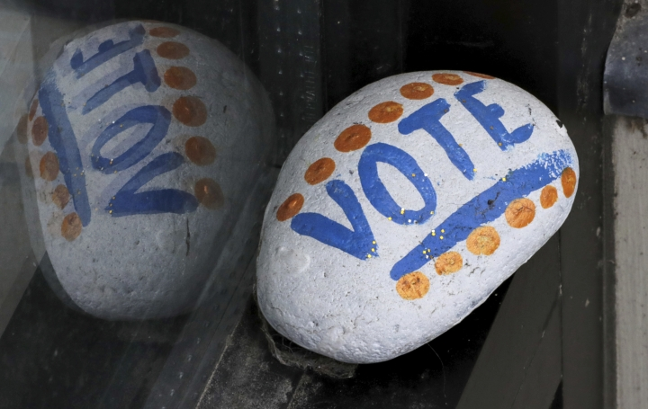 "FILE - In this March 22, 2019, file photo, a stone painted with the word ""VOTE"" rests on the window sill of an art gallery in Peterborough, N.H. More than half of Americans want major changes to the system of government, including about 1 in 10 who want a complete overhaul. That's according to a new survey by the University of Chicago Harris School for Public Policy and The Associated Press-NORC Center for Public Affairs Research showing that dissatisfaction with the government system is closely tied with policy concerns. (AP Photo/Charles Krupa, File)"