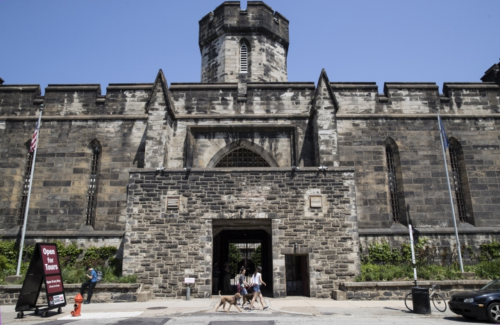 People walk past the Eastern State Penitentiary, Thursday, May 2, 2019, which is now a museum, in Philadelphia. The historic site has made a recreation of gangster Al Capone's 1929 cell. (AP Photo/Matt Rourke)