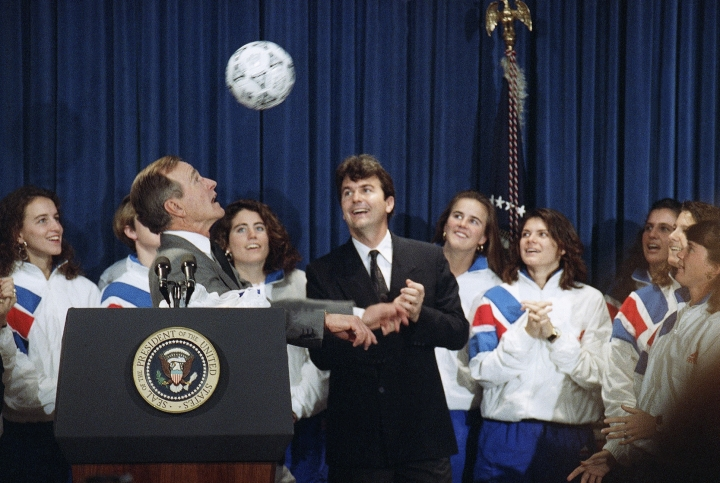 "FILE - In this Jan. 23, 1992, file photo, U.S. President George H. Bush heads a soccer ball while meeting the 1991 Women's World Cup soccer champions, in Washington. Anson Dorrance, coach of the team is at center. The 1999 and 2015 U.S. Women's World Cup teams have received plenty of attention and accolades over the years, but not much has been reported about the 1991 team that won the first Women's World Cup. ""Sports Illustrated's"" Grant Wahl is hoping to change that. The magazine is debuting a new podcast called ""Throwback"" with the first season focused on how the Women's World Cup started.(AP Photo/Barry Thumma, File)"