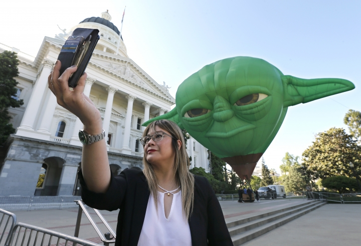 "State Sen. Ling Ling Chang poses for a selfie with a hot air balloon shaped like Yoda of Star Wars, outside the Capitol Thursday, May 2, 2019, in Sacramento, Calif. Chang, a Southern California Republican whose district is near Disneyland, joined other lawmakers in declaring May 4 as ""Star Wars Day.""(AP Photo/Rich Pedroncelli)"