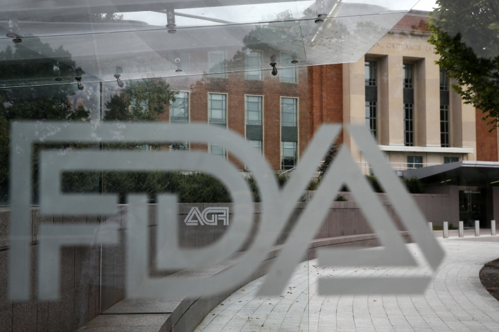 FILE - This Thursday, Aug. 2, 2018, file photo shows the U.S. Food and Drug Administration building behind FDA logos at a bus stop on the agency's campus in Silver Spring, Md. The FDA said Thursday, May 2, 2019, that a type of breast implant linked to a rare form of cancer will be allowed to stay on the market. (AP Photo/Jacquelyn Martin, File)