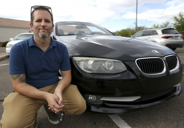 In this April 23, 2019, photo, Chris Williamson poses for a photo sitting next to his car in Phoenix. When Williamson was in the market for a new family car, a timely ad and conversations with a co-worker convinced him to try something out of the ordinary. He bought the BMW 3 Series convertible and covers the payments by renting it to strangers on a peer-to-peer car sharing app called Turo. It allows his family of seven to have a nicer car, essentially for free. (AP Photo/Ross D. Franklin)