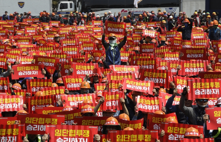 """In this May 1, 2019, photo, members of the Korean Confederation of Trade Unions hold up their banners during a May Day rally in Seoul, South Korea. Thousands of trade union members and activists are marking May Day by marching through Asia's capitals and demanding better working conditions and expanding labor rights. The signs read """"Let's win the wage struggle."""" (AP Photo/Ahn Young-joon)"""