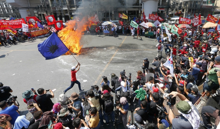 """In this May 1, 2019, photo, a protester runs around a burning effigy of President Rodrigo Duterte during a rally near the Presidential Palace in Manila, Philippines, to pay tribute to workers in celebration of International Labor Day. The workers scored Duterte allegedly for reneging in his campaign promise three years ago to end temporary hiring known as """"contractualization"""" or """"ENDO"""" (End of Contract). (AP Photo/Bullit Marquez)"""