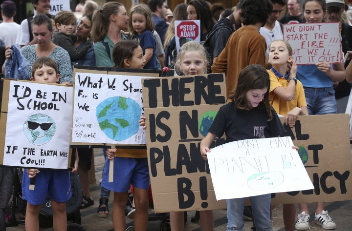 School kids hold handmade signs at a student organized protest at the office of former Australian Prime Minister Tony Abbott's office in Sydney, Australia, Friday, May 3, 2019. A federal election will be help on May 18. (AP Photo/Rick Rycroft)