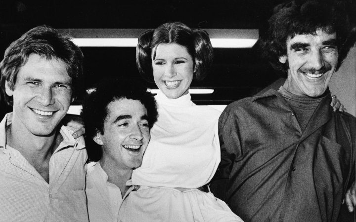 "ADDS NAME OF CARRIE FISHER'S CHARACTER AND BYLINE - FILE - In this Oct. 5, 1978, file photo, actors featured in the ""Star Wars"" movie, from left, Harrison Ford who played Han Solo, Anthony Daniels who played the robot C3P0, Carrie Fisher who played Princess Leia, and Peter Mayhew who played the Wookie, Chewbacca, are shown during a break from the filming of a television special presentation in Los Angeles. Mayhew, who played the rugged, beloved and furry Wookiee Chewbacca in the ""Star Wars"" films, has died. Mayhew died at his home in north Texas on Tuesday, April 30, 2019, according to a family statement. He was 74. (AP Photo/George Brich, File)"