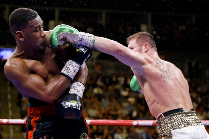 Canelo Alvarez, right, of Mexico, tries to hit Daniel Jacobs with a left during a middleweight title boxing match Saturday, May 4, 2019, in Las Vegas. (AP Photo/John Locher)