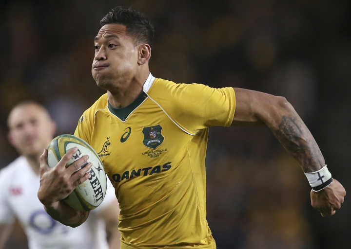 FILE - In this June 25, 2016, file photo, Australian rugby union player Israel Folau, wearing tape on his wrist adorned with a cross, runs toward the try line to score against England during their rugby union test match in Sydney. The 30-year-old Folau will appear before a code of conduct hearing at Rugby Australia's headquarters in Sydney to determine the playing future of the star Wallabies fullback on Saturday, May 4, 2019. (AP Photo/Rick Rycroft, File)