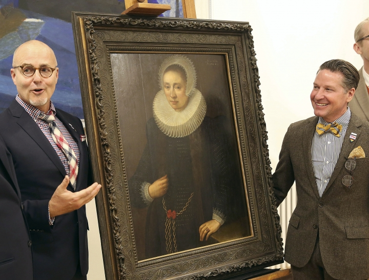 "A Los Angeles couple, Craig Gilmore, left, and David Crocker, pose in front of a 17th painting, ""Portrait of a Lady"" by the Flemish artist Melchior Geldorp at the National Museum in Warsaw, Poland, Friday, April 5, 2019. The two were dumbfounded when Homeland Security agents showed up at their home in 2016 with news the work been looted by the Nazis from Poland's National Museum during World War II. (AP Photo/Czarek Sokolowski)"
