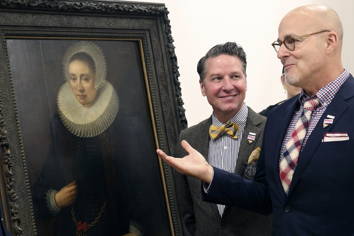 "A Los Angeles couple, Craig Gilmore, right, and David Crocker, pose in front of a 17th painting, ""Portrait of a Lady"" by the Flemish artist Melchior Geldorp at the National Museum in Warsaw, Poland, Friday, April 5, 2019. The two were dumbfounded when Homeland Security agents showed up at their home in 2016 with news the work been looted by the Nazis from Poland's National Museum during World War II. (AP Photo/Czarek Sokolowski)"