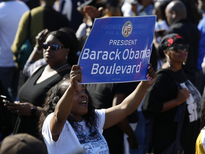"A woman holds a banner of the Obama Boulevard in Los Angeles, Saturday, May 4, 2019. The Obama Boulevard will replace Rodeo Road, a 3 ½-mile street that runs across the city's historic black neighborhood. It will also intersect with Martin Luther King Jr. Boulevard and further establish a ""presidential row"" that includes Washington, Adams and Jefferson boulevards. (AP Photo/Damian Dovarganes)"