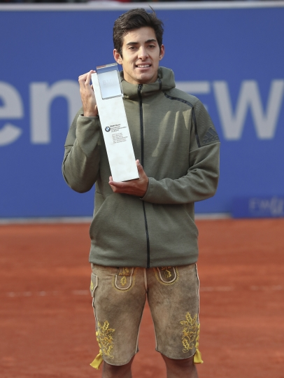 Cristian Garin of Chile poses with the trophy of the Munich ATP tennis tournament wearing a pair of traditional Bavarian pants after defeating Italy's Matteo Berrettini in the final match, in Munich, Germany, Sunday, May 5, 2019. (AP Photo/Matthias Schrader)
