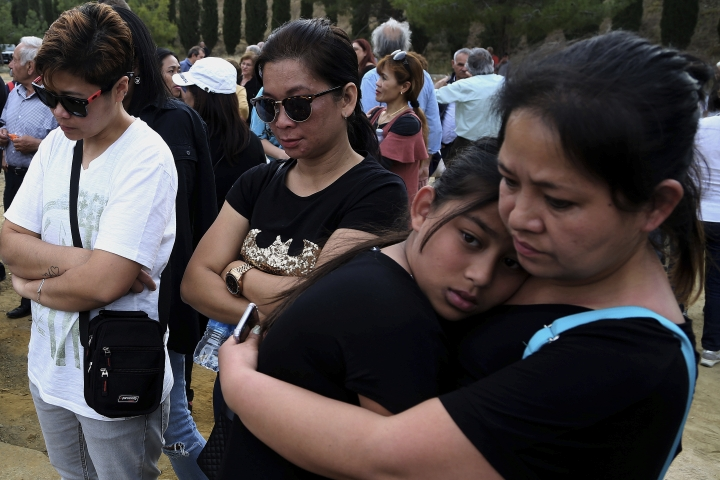 People attend a memorial for victims at the mineshaft where two female bodies were found near the village of Mitsero outside of the capital Nicosia, Cyprus, Sunday, May 5, 2019. Cyprus police spokesman Andreas Angelides says investigators hunting for bodies dumped by a suspected serial killer pulled a suitcase containing decomposing human remains from a toxic lake. (AP Photo/Petros Karadjias)