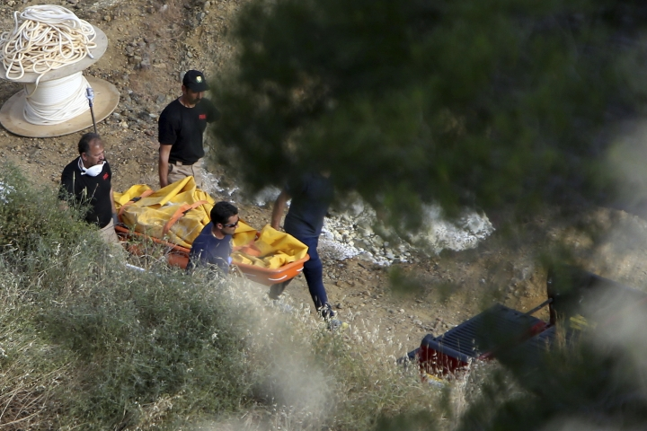 Cyprus Special Disaster Response Unit carry a suitcase after it was retrieved from a man-made lake near the village of Mitsero outside of the capital Nicosia, Cyprus, Sunday, May 5, 2019. Cyprus police spokesman Andreas Angelides says investigators hunting for bodies dumped by a suspected serial killer pulled a suitcase containing decomposing human remains from a toxic lake. (AP Photo/Petros Karadjias)