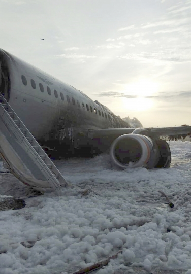 The Sukhoi Superjet 100 aircraft of Aeroflot Airlines is covered in fire retardant foam after an emergency landing in Sheremetyevo airport in Moscow, Russia, Sunday, May 5, 2019. Over a dozen people died Sunday in a fiery airplane accident at Moscow's Sheremetyevo Airport, a spokeswoman for the Russian Investigative Committee said. (Moscow News Agency photo via AP)