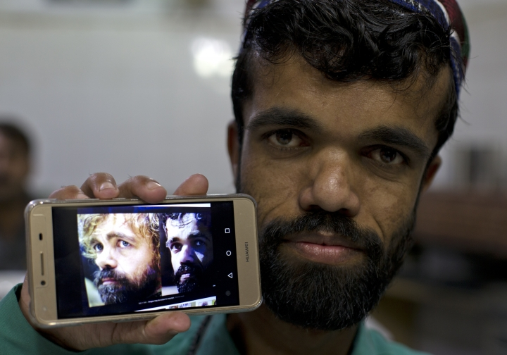 "In this Friday, May 3, 2019 photo, Rozi Khan, a 26-year-old Pakistani shows his picture on his phone next to a picture of the U.S. actor Peter Dinklage who plays Tyrion Lannister on the TV series ""Game of Thrones,"" in Rawalpindi, Pakistan. Khan does not only have a similar look, haircut and beard as Dinklage, but the two share a genetic condition that results in small stature. (AP Photo/B.K. Bangash)"