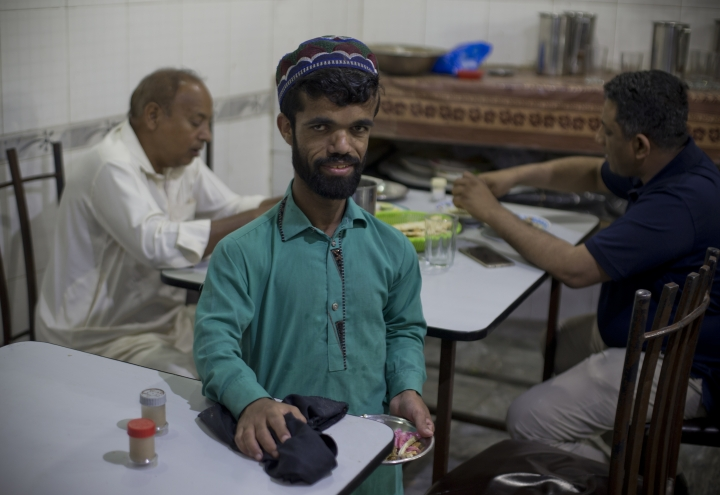 """In this Friday, May 3, 2019 photo, Rozi Khan, a 26-year-old Pakistani who shares a resemblance to the U.S. actor Peter Dinklage, 49, who plays Tyrion Lannister on the TV series """"Game of Thrones,"""" works as a waiter in a small cafe in Rawalpindi, Pakistan. Khan does not only have a similar look, haircut and beard as Dinklage, but the two share a genetic condition that results in small stature. (AP Photo/B.K. Bangash)"""