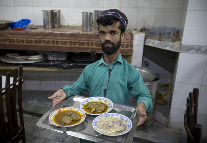 "In this Friday, May 3, 2019 photo, Rozi Khan, a 26-year-old Pakistani who shares a resemblance to the U.S. actor Peter Dinklage, 49, who plays Tyrion Lannister on the TV series ""Game of Thrones,"" works as a waiter in a small cafe in Rawalpindi, Pakistan. Khan does not only have a similar look, haircut and beard as Dinklage, but the two share a genetic condition that results in small stature. (AP Photo/B.K. Bangash)"